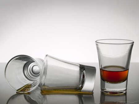 distilled: Tre colpi di whiskey in bianco su sfondo grigio piano