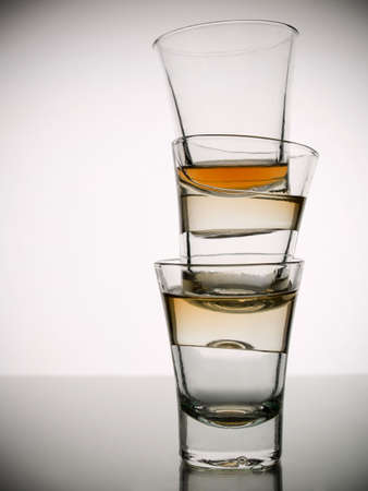 A pile of three almost empty shots of whisky on white background over gray floor