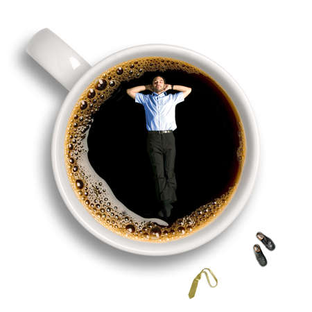 Top view of a young business man taking a nap inside an isolated cup of coffee with his tie and shoes sitting aside. photo