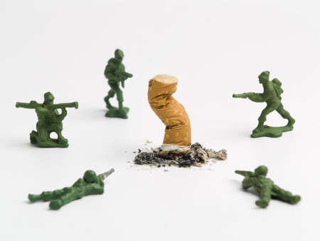 damaging: A cigarette butt surrounded by a group of toy soldiers.