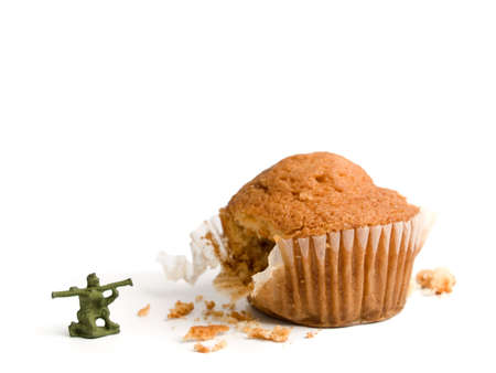 bazooka: A toy soldier shooting his bazooka at a muffin. A conceptual image about the importance of a healthy lifestyle. Stock Photo