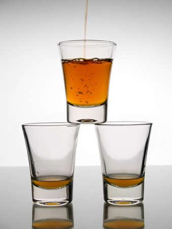 rhum: A shot being poured over other two almost empty shots. Stock Photo