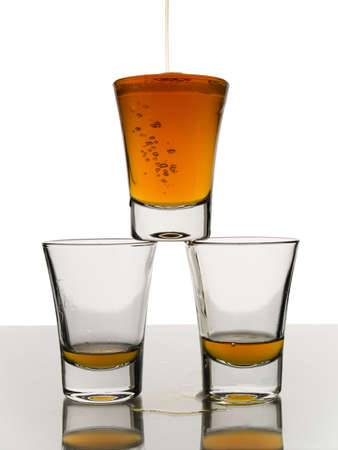 A shot being poured over two almost empty shots. photo