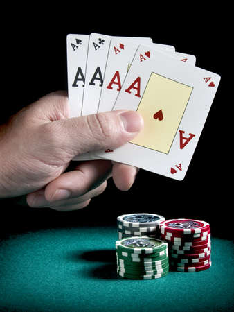 A mans hand holding four aces over three piles of differents colors chips on a green felt. photo