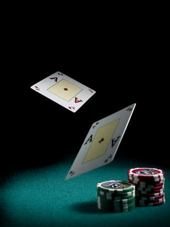 poker: Two aces flying over a green felt with three piles of differents colors chips.