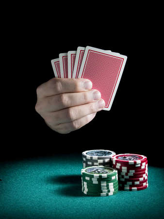 A mans hand holding four cards over three piles of differents colors chips on a green felt.