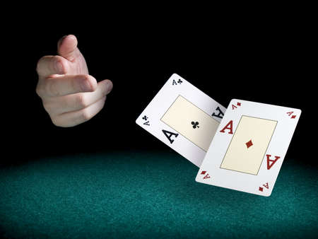 poker cards: A mans hand throwing two aces over a green felt. Stock Photo