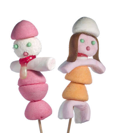 jelly head: A male and a female figurin made out of candies on a stik over a white background.