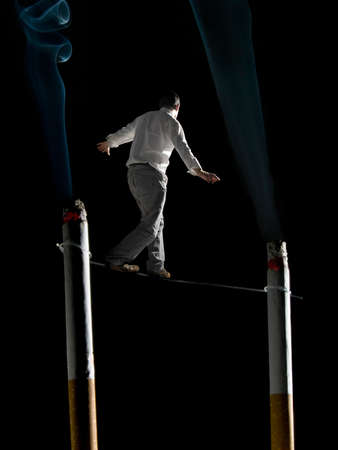 vices: A man walking a tightrope suspended  between two big cigarettes. A conceptual image about the health risks of smoking.