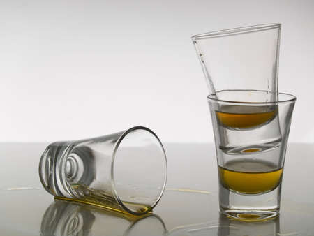 Three shots of whiskey on white background over gray floor.
