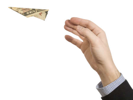 A mans hand throwing a paper plane made of a ten dollar bill. photo