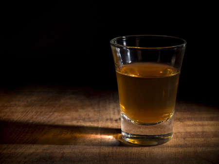 A single shot of an aged liquor over a wooden table. Stock Photo - 3596622