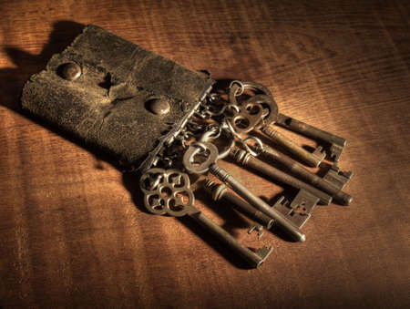 tarnish: An old leather keyring over a wooden table.