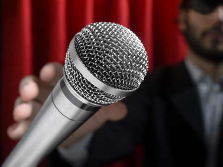 comedian: A youg man on stage about to grab a microphone.