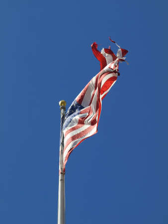 A ripped american flag waving over a blue sky. photo