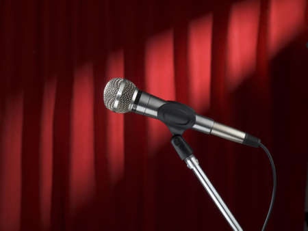 A microphone on stage over a red background. Stock Photo