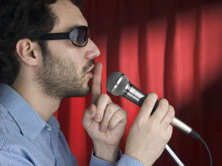 A young man with sunglasses hushing the audience on the mic. photo