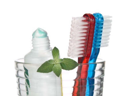 Toothbrushes, toothpaste and mint leaves in a glass over white background.