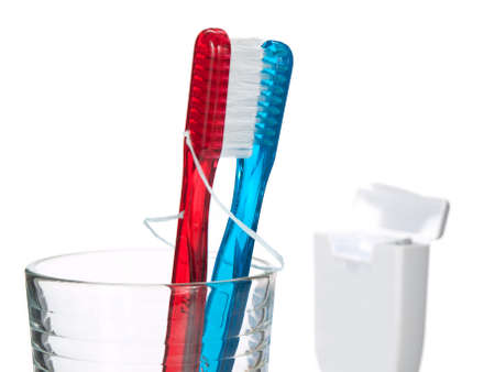 Two toothbrushes hugging and kissing passionately in a glass, and a opened box of dental thread on a side. Isolated on white. photo