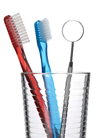 Two toothbrush and a mouth mirror in a glass. photo