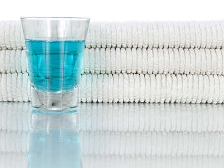 mouthwash: A glass full of mouthwash on a background of clean and white towels.