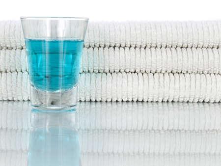 enjuague bucal: Un vaso lleno de enjuague bucal sobre un fondo de toallas limpias y blancos. Foto de archivo