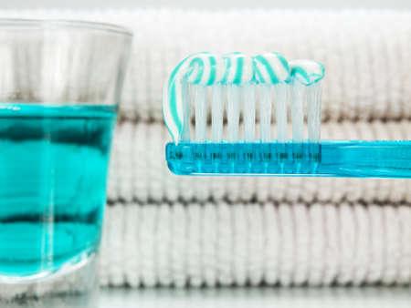 enjuague bucal: Un cepillo de dientes de color azul con pasta de dientes, un vaso lleno de enjuague bucal y toallas en el fondo.