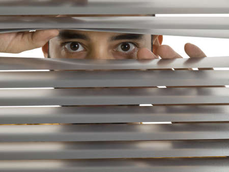 snooping: A man looks to the camera through the blinds.
