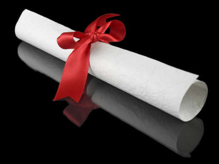 certificate: Diploma with a red silk ribbon, isolated on black background. Stock Photo