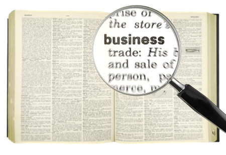 creditors: A magnifying glass on the word BUSINESS on a dictionary.