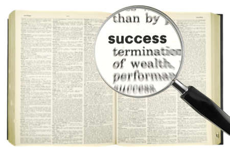 A magnifying glass on the word SUCCESS on a dictionary.