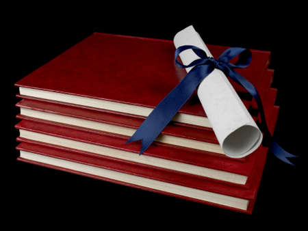 baccalaureate: A diploma with blue ribbon over several books. Isolated on black.
