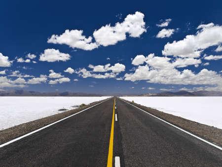 A straight road across an open salt mine.