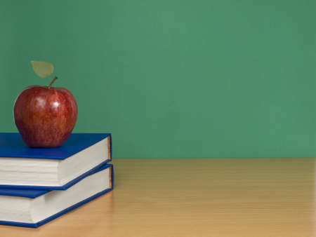A blank chalkboard with an apple over books. photo