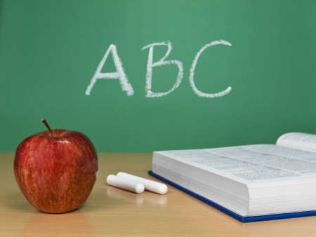 chalks: ABC written on a chalkboard with an apple, a book and some chalks. Stock Photo