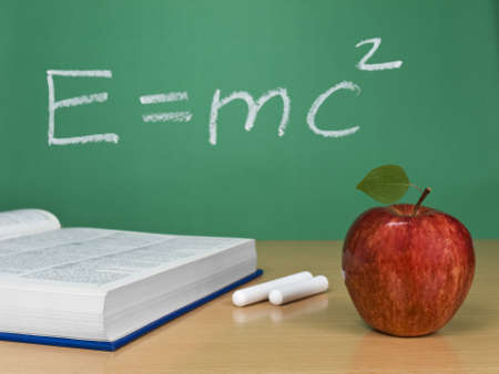 Einsteins formula on a chalkboard with an apple, a book and some chalks. Stock Photo