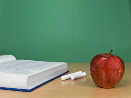 A blank chalkboard with an apple, a book and some chalks. photo