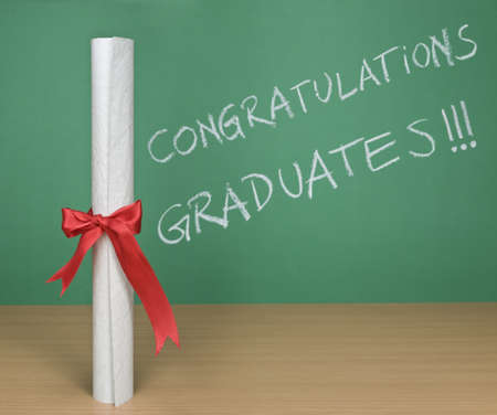 Congratulations graduates written on a chalkboard with a diploma on forefround. Stock Photo