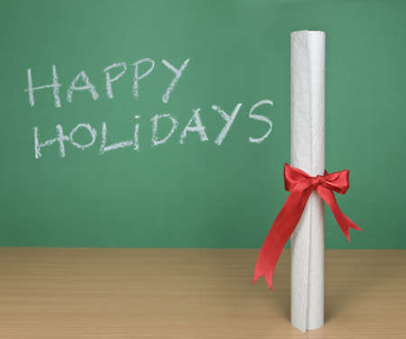 Happy holidays written on a chalkboard with a diploma on forefround. Stock Photo