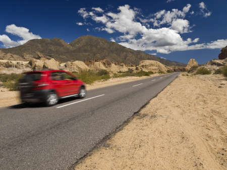 arid: A fast car on the road in a arid and rocky landscape.