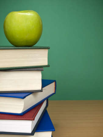 An apple on top of a pile of books. Blank chalkboard on the background. Stock Photo