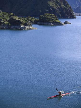 A kayaker paddling across a peaceful lake. photo