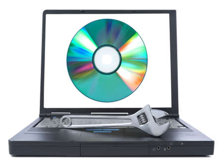 computer problem: Isolated black laptop with a spanner over it and a digital disc on the screen.