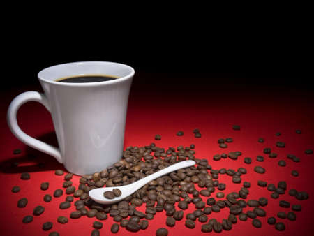 A cup of tasty coffee and some coffee beans spread arround. photo
