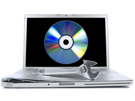 operative system: Damaged laptop with a spanner over it and a digital disc on the screen. Isolated on white.