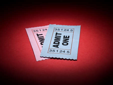 Close up shot of two generic admission tickets over red background.