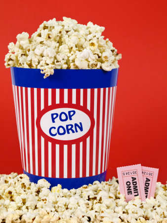 A popcorn bucket over a red background. Movie stubs sitting over the popcorn. Stock Photo - 4541305