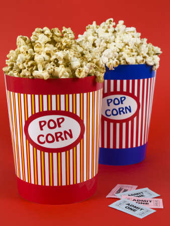 Two popcorn buckets over a red background. Movie stubs sitting aside. Stock Photo - 4541303