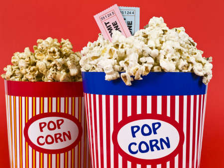 Two popcorn buckets over a red background. Movie stubs sitting over the popcorn. photo