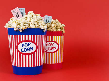 Two popcorn buckets over a red background. Movie stubs sitting over the popcorn. Stock Photo - 4541301